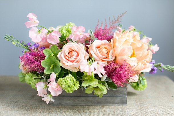 Coral Charm Peonies, purple Stocks, red Astilbe, Pearl Avalanche Rose, green Hellebore,  Senecio foliage, silver Brunia foliage and white Sweet Pea centrepiece