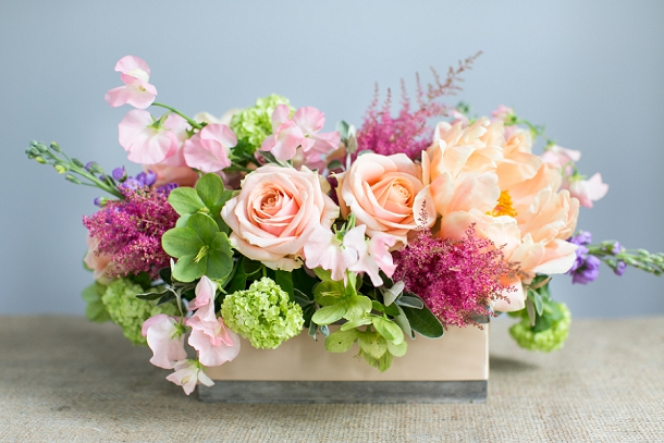 Coral Charm Peonies, purple Stocks, red Astilbe, Pearl Avalanche Rose, green Hellebore,  Senecio foliage, silver Brunia foliage and white Sweet Pea centrepiece with peach ribbon