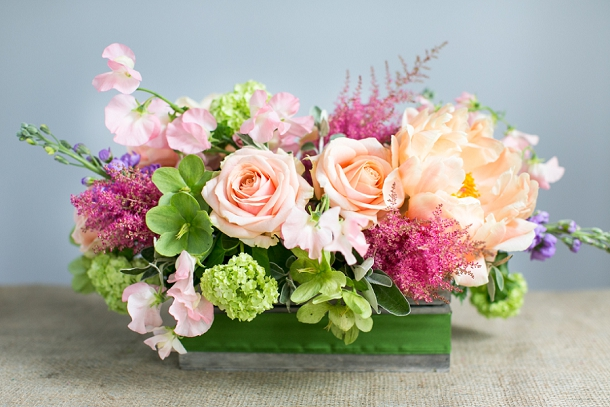 Coral Charm Peonies, purple Stocks, red Astilbe, Pearl Avalanche Rose, green Hellebore,  Senecio foliage, silver Brunia foliage and white Sweet Pea centrepiece with green ribbon