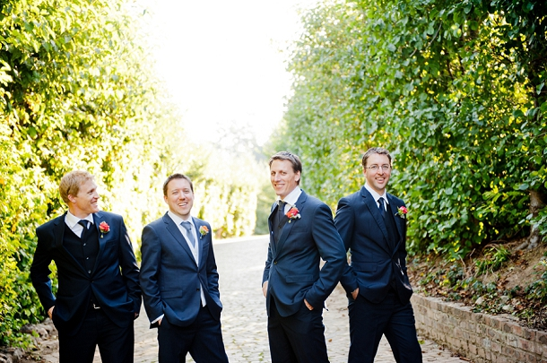 navy suited groomsmen with coral buttonholes