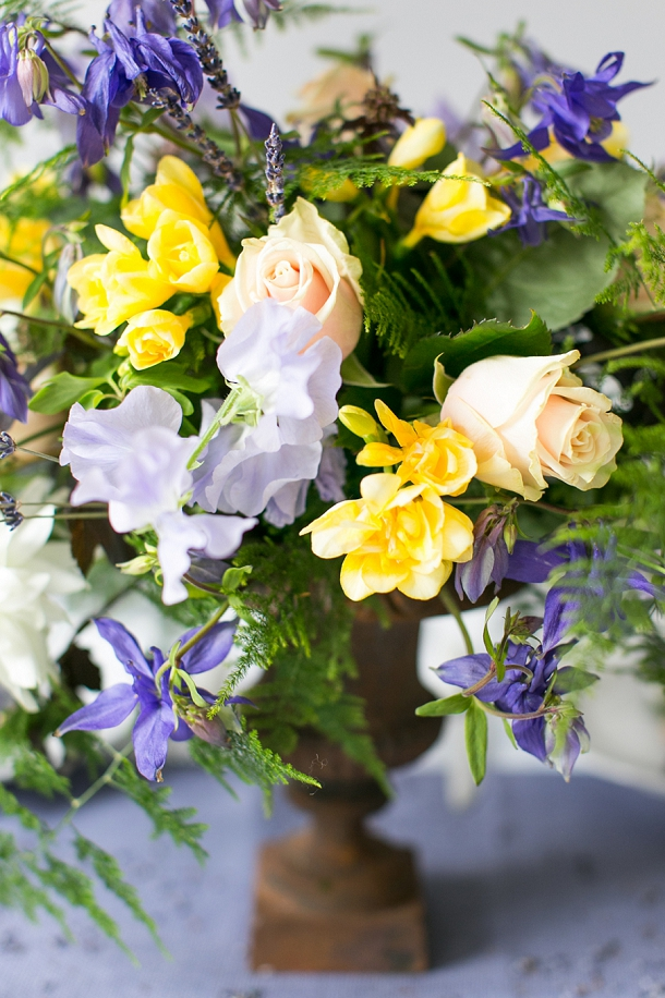 Rusty urn filled with yellow Freesia, lilac Sweet Peas and Scabious, purple Aquilegia, Lavender, pale pink Sweet Avalanche Roses and Asparagus Fern