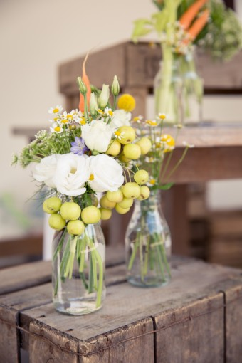 Yellow and white flowers in bottles with chillis