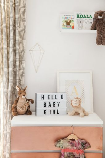 nursery dresser top styled with soft toys and prints
