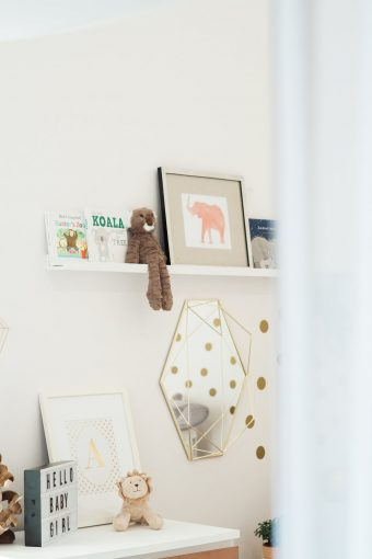 nursery shelf with books prints and soft toys