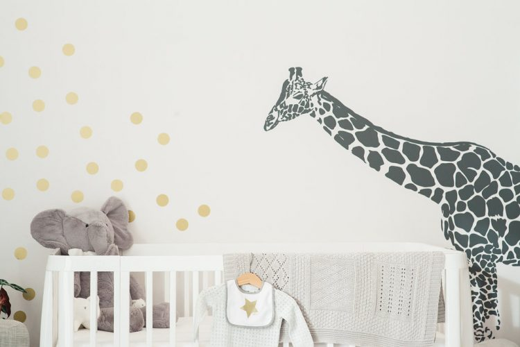 cute grey star baby outfits hung on white retro crib
