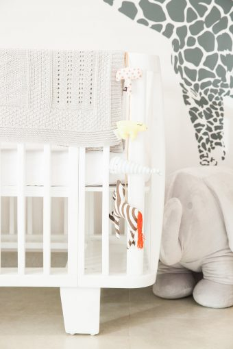 retro white nursery crib and soft toys