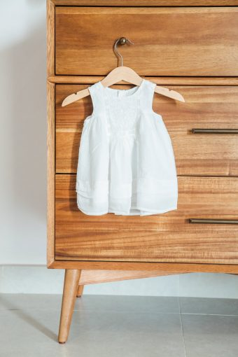 baby girls dress hung on retro sideboard