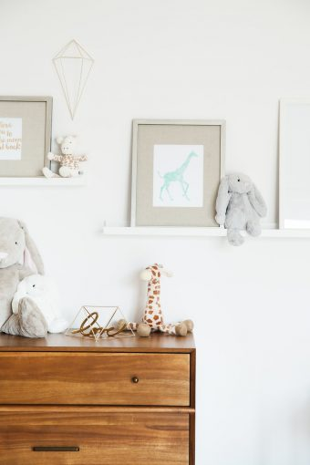retro nursery dresser styled with soft toys and prints
