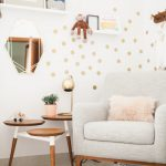 modern luxe nursery style decor with grey retro armchair and gold dot wall