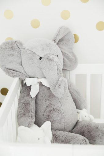 large soft toy elephant sat inside babies crib nursery tour