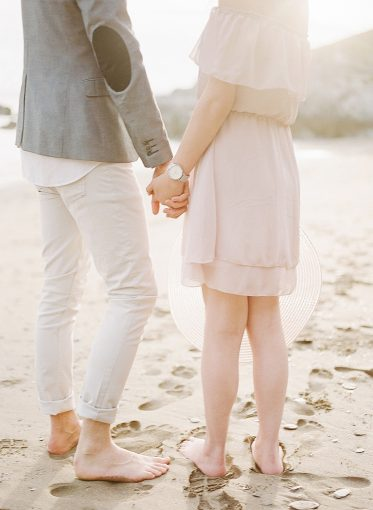 couple holding hands on the beautiful cornwall beach setting