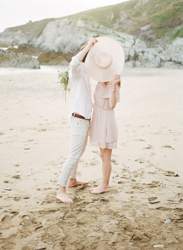 couple on the beach hide behind a sun hat