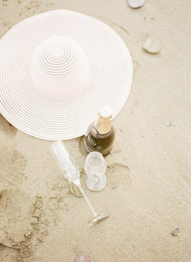 chanpagne, glasses and a sun hat sat on the sand