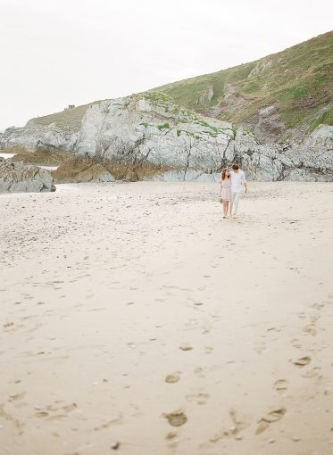 couple take a walk along the cornwall beach holding hands