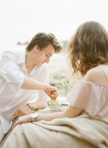 couple sit together on a rock as they picnic on the beach