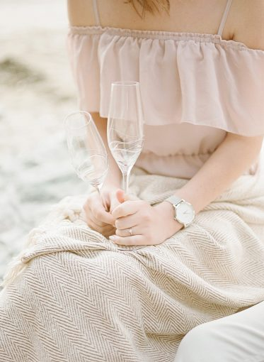 newly engaged woman is wrapped in a pretty blanket and holding champagne glasses as they picnic on the beach