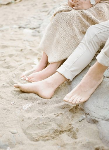 couples bare feet in the sand on the beach