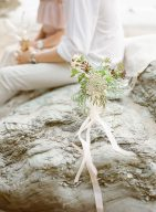 Pretty little bouquet of foraged flowers displayed on a rock on the beach