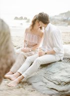 couple share a romantic kiss as they picnic on the beach