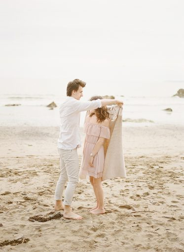 Couple on the beach wrap themselves in a blanket for warmth