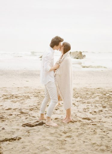 Couple on the beach kiss and wrap themselves in a blanket for warmth