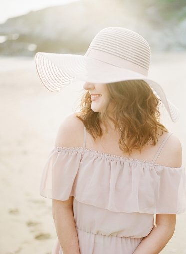 light filled portrait of woman sat on the beach wearing a wide brim sun hat