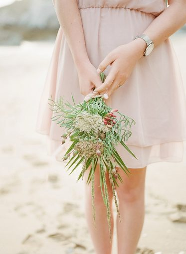 Pretty little bouquet of foraged flowers held by woman wearing pink dress