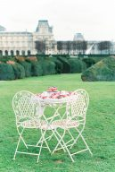 bistro table and chairs set within a garden in Paris city
