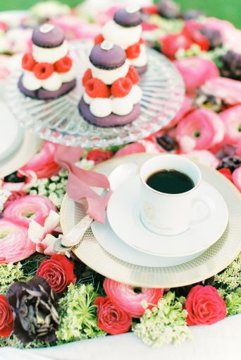 A table covered in florals and displaying vintage cups and saucers and desserts