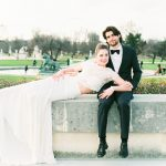 Bride and Groom sat on a wall in the gardens of Paris