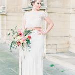 Bridal portriat wearing a chic two piece and carrying a bouquet