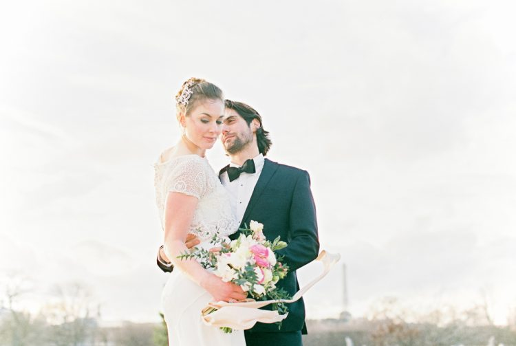 bride and groom with the Parisian sky and cityline behind them