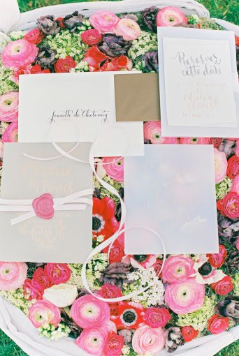 wedding stationery sat on top of a bed of florals