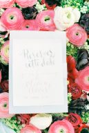 wedding stationery invitation sat on top of a bed of flowers