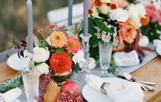 wedding table setting with autumn colours pomegranites and tall grey tapered candles