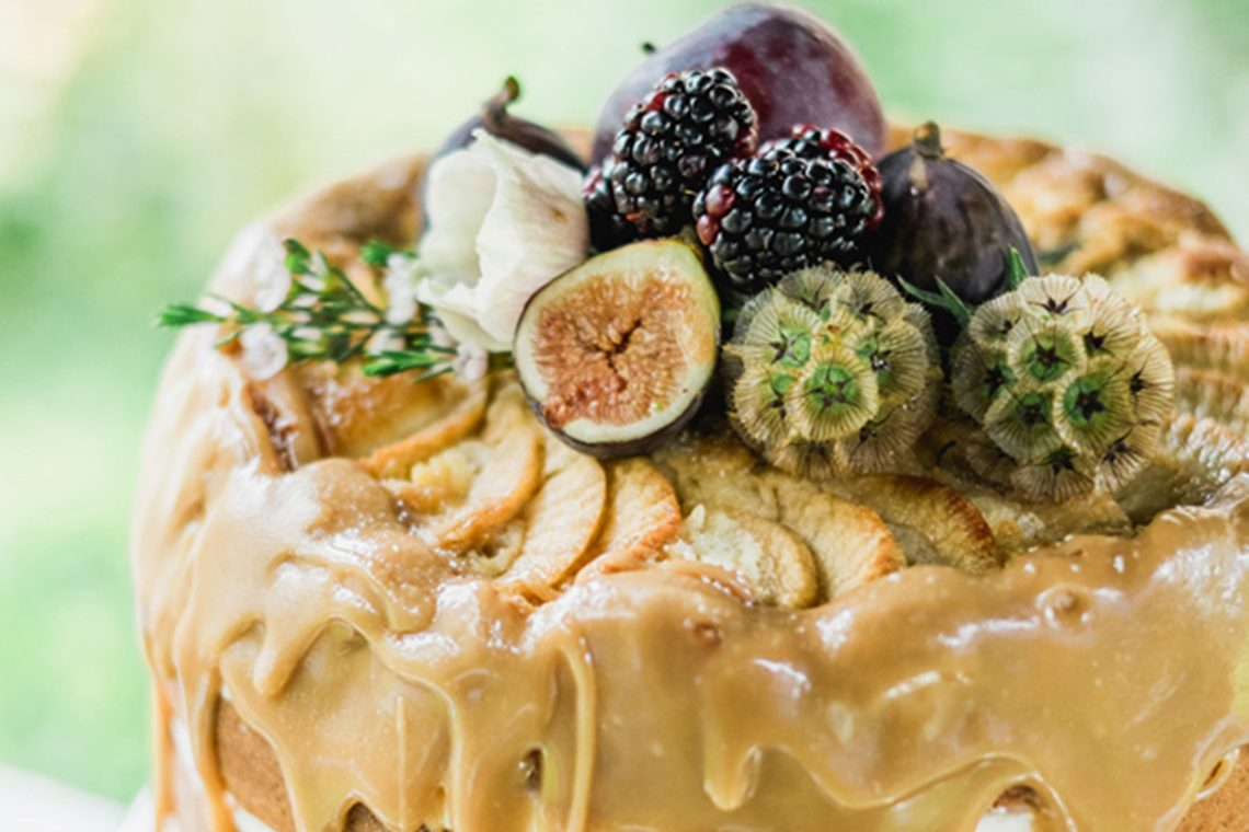 wedding cake with dripping caramel sauce topping and with berries and figs arranged as a display on top