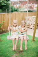 sisters sit together on the pretty wooden swing in the garden
