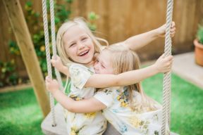 sisters play and hug on the swing in the garden