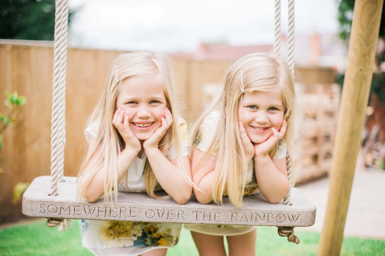 sisters pose on the swing in the garden
