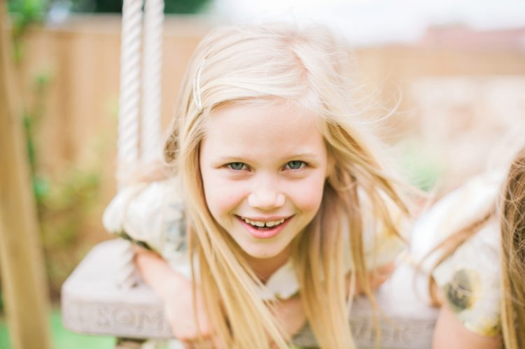 portrait playing on a swing in the garden