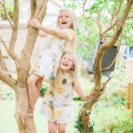 sisters climbing a little tree in the summer garden