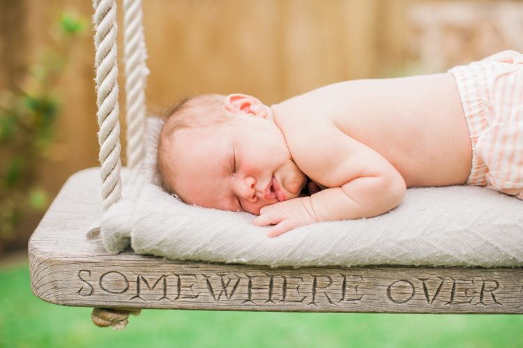 newborn baby portrait lay upon a beautiful wooden swing and blanket