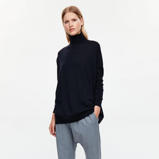 chic simple black jumper by Cos worn with grey tailored trousers