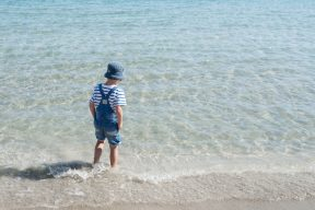 Young boy dips his feat into the Aegean sea pebble beach