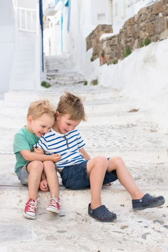 Hannahs boys sit and hug on the beautiful bright steps of a winding street in the aegean islands