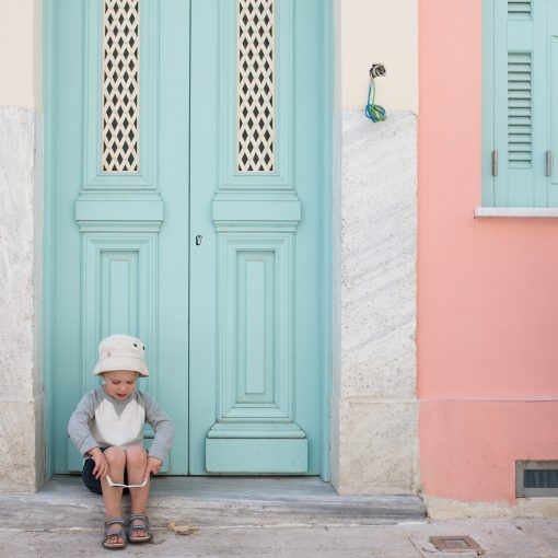 pink washed buildings and turquoise door of the aegean islands