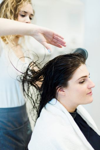 hair stylist styling a clients hair at blush and blow london