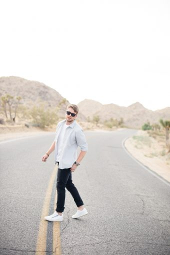 Groom to be wearing jeans and shirt and sunglasses