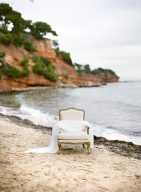 beautiful antique style cream chair sat n a pebbled beach with a wedding veil draped upon it
