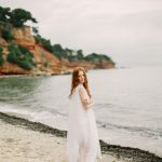 deicate bridal style look with a flowing wedding gown and set on the bech